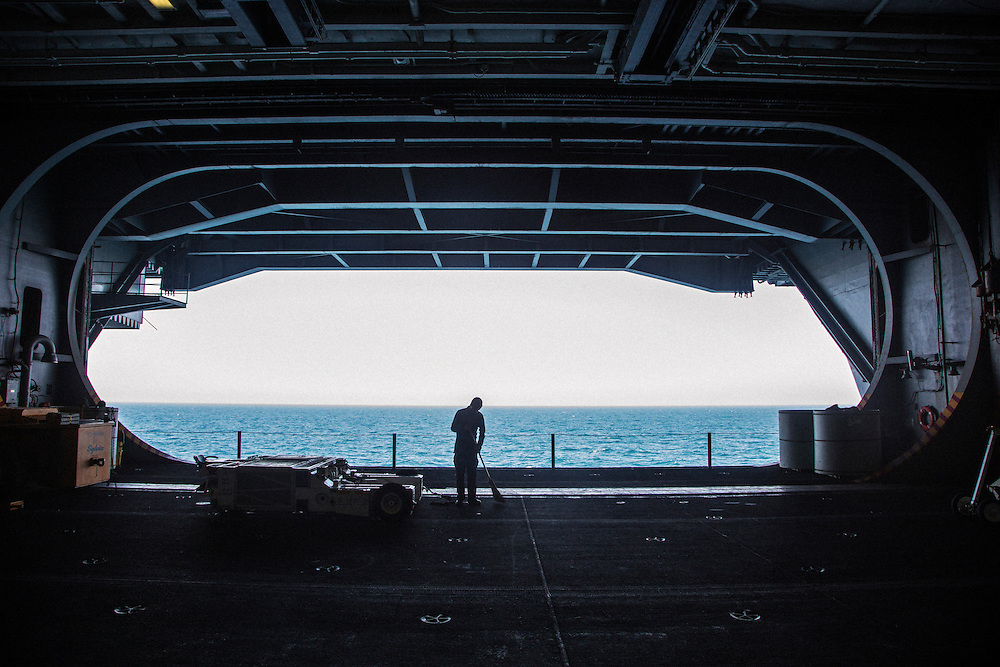 A crew member cleans on the hanger deck next to the opening for one of four massive aircraft elevators<br /> <br /> Aboard the USS Harry S. Truman operating in the Persian Gulf. February 25, 2016.<br /> <br /> Matt Lutton / Boreal Collective for Mashable