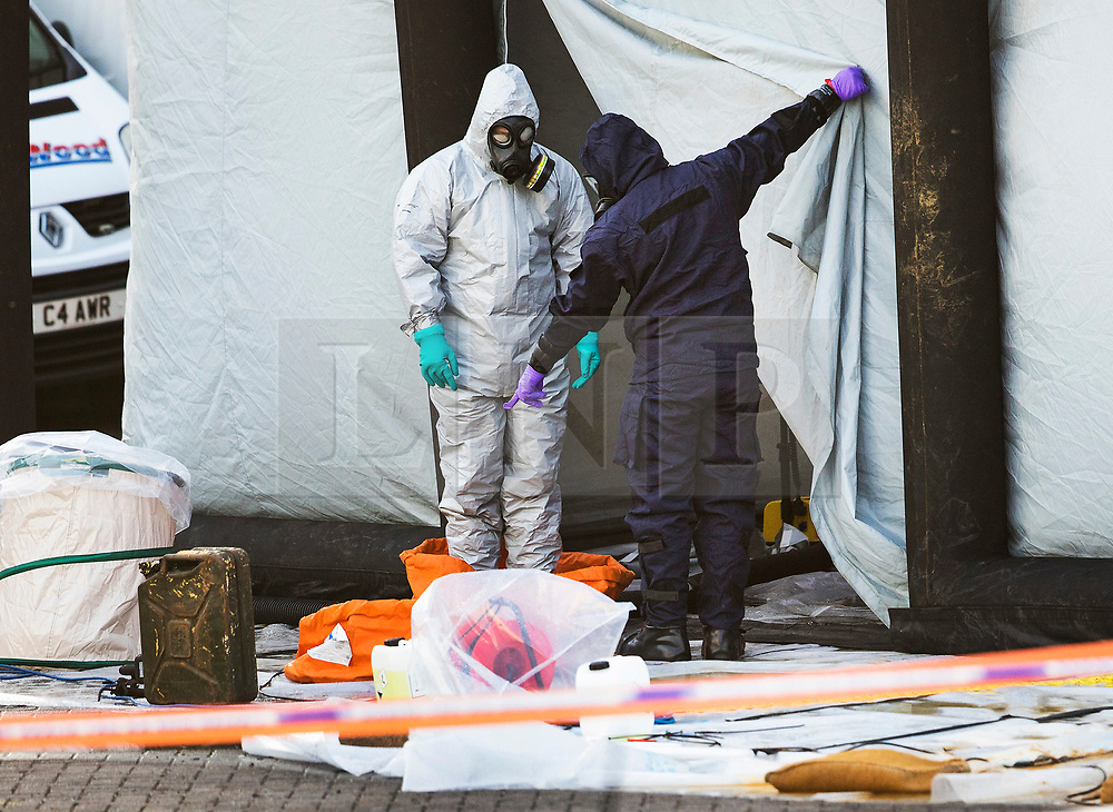 © Licensed to London News Pictures. 15/03/2018. Alderholt, UK. Police in protective overalls and a gas masks emerge from a tent erected at Ashley Wood Recovery in Salisbury where the car belonging to former Russian spy Sergei Skripal was taken after he and his daughter Yulia were poisoned with nerve agent. The couple where found unconscious on bench in Salisbury shopping centre. A policeman who went to their aid is currently recovering in hospital. Photo credit: Peter Macdiarmid/LNP