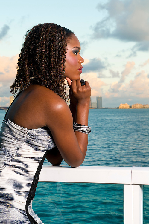 Young african american woman meditates in a terrace during sunset with the ocean in the background.