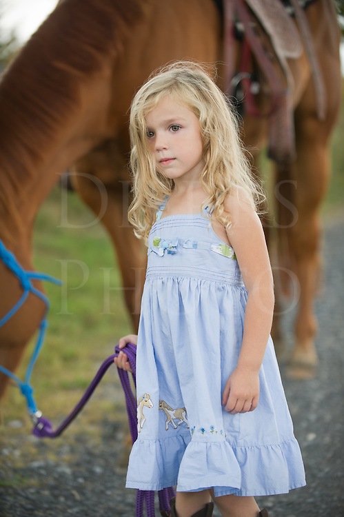 Little blonde girl leading her big horse down a country lane, three years old.