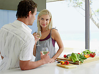 Young couple holding wineglasses talking in kitchen