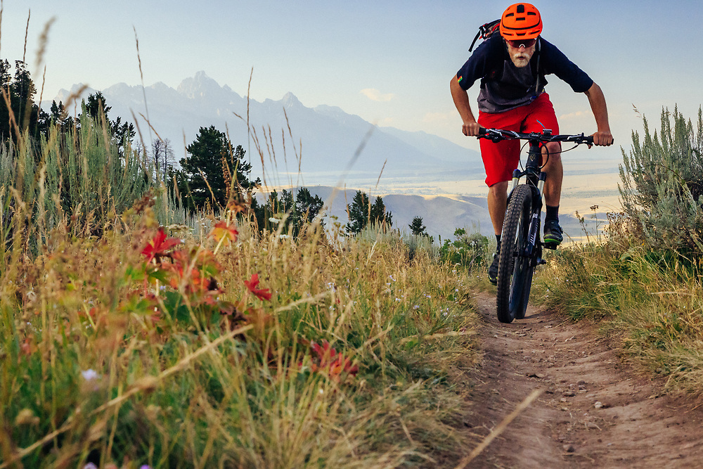 Andrew Whiteford rides the top of the Ferrin's Trail with the sun setting over Grand Teton in the distance near Jackson, Wyoming.