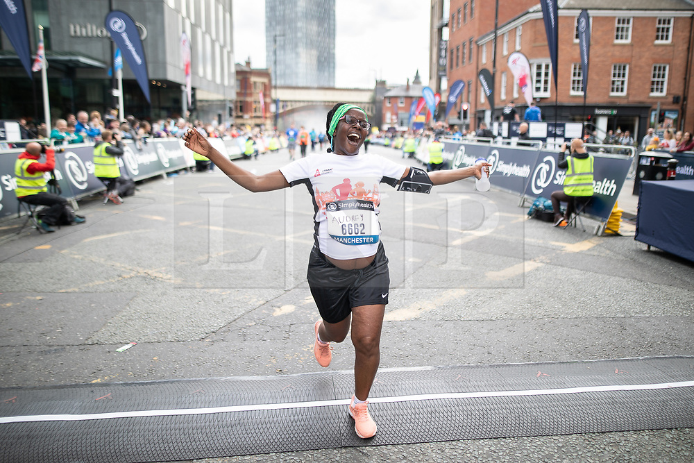 © Licensed to London News Pictures . 19/05/2019. Manchester, UK. AUDREY NUKOSARA (37) , who is 29 weeks pregnant , completes the run . Participants at the finish line of the 10k run in the Great Manchester Run in Manchester City Centre . Photo credit : Joel Goodman/LNP