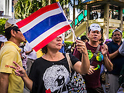 "09 JUNE 2013 - BANGKOK, THAILAND:   A member of the White Mask protest movement waves a Thai flag on the plaza in front of Central World in Bangkok. The White Mask protesters wear the Guy Fawkes mask popularized by the movie ""V for Vendetta"" and the protest groups Anonymous and Occupy. Several hundred members of the White Mask movement gathered on the plaza in front of Central World, a large shopping complex at the Ratchaprasong Intersection in Bangkok, to protest against the government of Thai Prime Minister Yingluck Shinawatra. They say that her government is corrupt and is a ""puppet"" of ousted (and exiled) former PM Thaksin Shinawatra. Thaksin is Yingluck's brother. She was elected in 2011 when her brother endorsed her.     PHOTO BY JACK KURTZ"