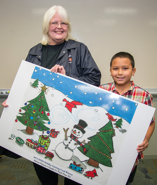 Park Place Elementary School art teacher Kathleen McAuliffe poses with Adrian Pizarro and his winning design during the Houston ISD official holiday card reception, November 8, 2013.