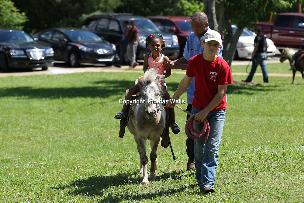Serenity Calvin, 3, enjoys a pony pony ride as part of the Hillsdale Apartments Summer Kick-Off Thursday morning in Tupelo.