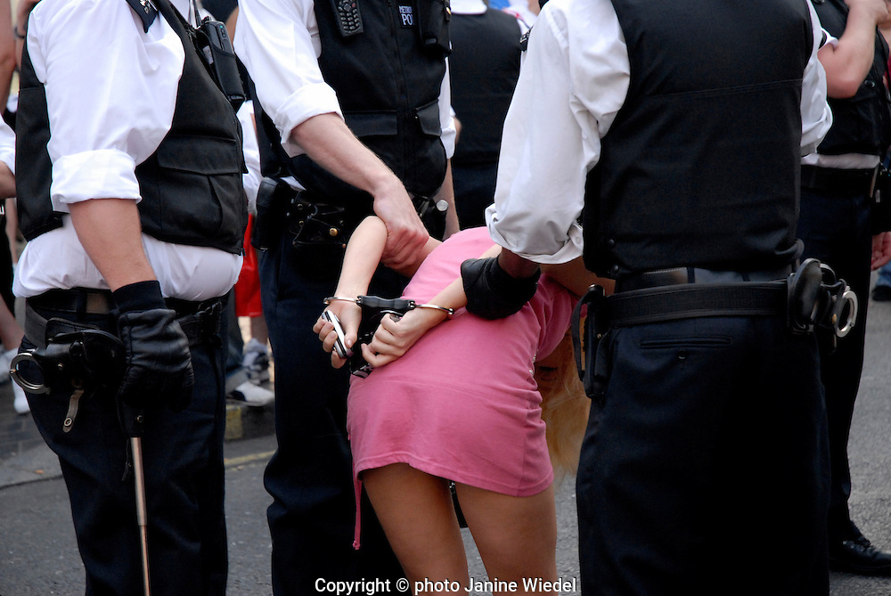 Police officers holding handcuffing and arresting young female football fan in Central London after England lost in the World Cup 2006.