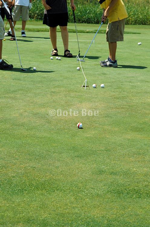 4 kids playing golf