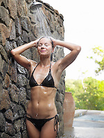 Young woman having shower by stone wall outdoors