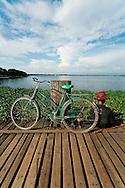 Man fishing at U Bein bridge with his bike parked near him