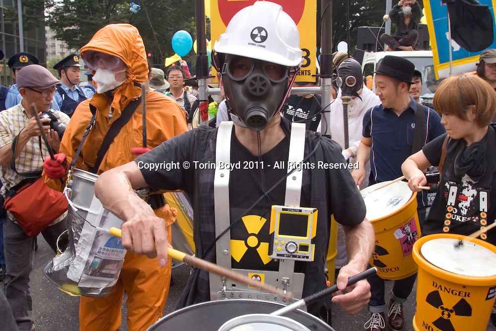 These are anti-nuke demonstrators taking to the streets of Tokyo's Shinjuku district to protest Japan's nuclear energy policy and anger against the Tokyo Electric Power Corp (TEPCO). This took place on June 11, 2011, exactly three months after the Fukushima Daichi Power Plant nuclear disaster and involved some 4000 demonstrators and nearly the same number of police. This and other demonstrations were staged across Tokyo involving tens of thousands demonstrators. TEPCO is the huge Japanese energy company responsible for the Fukushima disaster which has now been officially declared as having experienced a meltdown to two of it's reactors on March 11, 2011 when a tsunami struck it. This demo and others took place in Tokyo during afternoon and rush hour periods and was purposely intended to disrupt the city to call attention to their anti-nuke cause. However, this Shinjuku demo was very peaceful and had more of a festival or even carnival like atmosphere. This included heavy metal bands performing from trucks, traditional Japanese street musicians (called Chindoya), rap and reggae singers, as well as the demonstrators banging drums and shouting antinuclear slogans . The powerful March 11, 2011 earthquake and tsunami has officially killed 15,000 people, but an additional 8,300 are still missing.