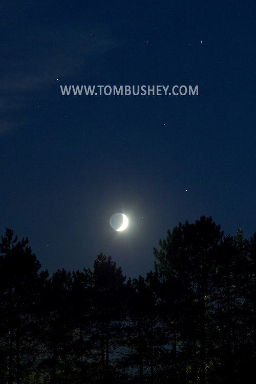 Middletown, New York - The crescent moon is joined in the western sky by the planets Mars, upper left, Saturn, upper right, and the bright star Spica, lower right after sunset on  Aug. 212012.