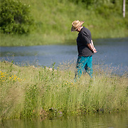 Woman walking through the tall grass at the public boat landing on the Union River. Ellsworth, Maine