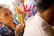 "14 MARCH 2006 - PHNOM PENH, CAMBODIA: People crowd into a small pagoda in front of the Royal Palace in Phnom Penh, Cambodia to pray. The pagoda serves as the ""spirit house"" of the palace. The Cambodians (and Thais) build small spirit houses, which have great religious significance, in front of the homes and usually businesses. They pray at the spirit homes and frequently leave small offerings of fruit and small change in them. The spirit house for the Palace has become a public shrine and there are usually people there praying, leaving donations and lighting incense. Photo by Jack Kurtz / ZUMA Press"