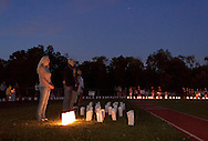 Goshen, New York - People stand inside and around the track, which is lined with luminaria in remembrance of cancer victims, during the Relay for Life at Goshen High School on June 16, 2012. The Relay for Life is the American Cancer Society's signature fundraising event. Participants celebrate the lives of people who have battled cancer, remember loved ones lost, and fight back against the disease by raising money.
