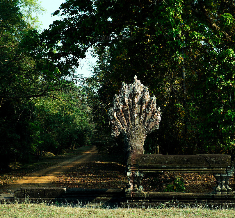 Angkor Wat, Naga figure on fence surrounding temple terrace, dirt road into forest beyond.