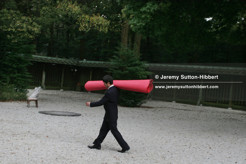 A photographer's assistant carries a red carpet for a photo shoot, in the grounds of Meiji Jingu shinto shrine, Tokyo, Japan.