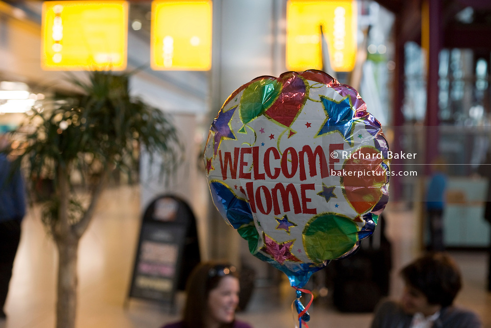 "A helium-filled Welcome Home balloon floats in the air in Heathrow Airport's Terminal 5 arrivals hall. Three families have gathered to meet their respective sons who have been travelling around the world during their university gap year sabbatical trip of a lifetime. Floating upwards, the balloon is brightly coloured amid the hectic concourse where other relatives greet their loved-ones after months away from home on their adventures. This is a tradition practised across the world's airports where families are separated by the need to travel or work in other countries and the emotion of meeting again after long absences is always hard. From writer Alain de Botton's book project ""A Week at the Airport: A Heathrow Diary"" (2009)."