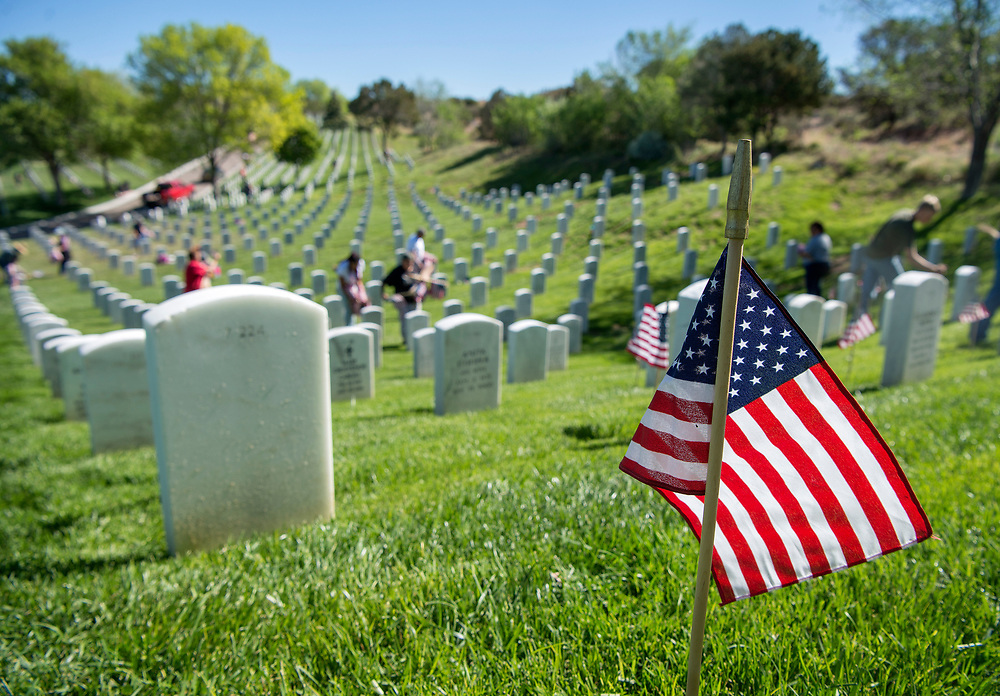 em052617d/a/Around 100 volunteers plant flags on graves at the Santa Fe National Cemetery on Friday May 26, 2017. The flags on the over 58,000 graves at the cemetery will be there for the Memorial Day weekend as well as events on Monday. (Eddie Moore/Albuquerque Journal