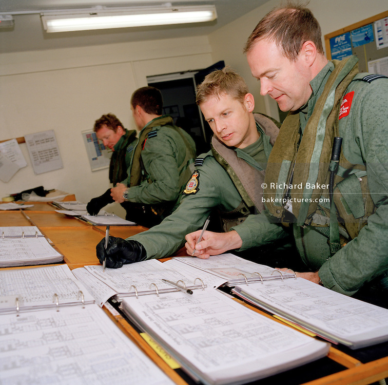 Pilots of the 'Red Arrows', Britain's Royal Air Force aerobatic team sign paperwork after winter training flight at RAF Scampton