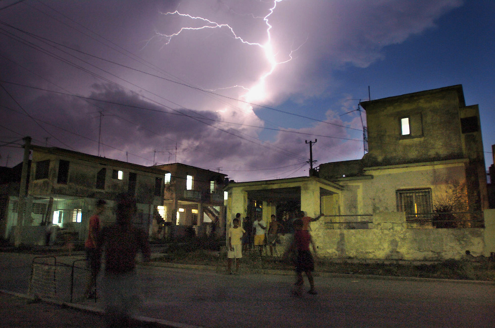 Children play soccer in the street as lightning flashes across the sky Wednesday, May 2, 2007 in the Lawton area Havana, Cuba. Most children do not have the luxury of playing with a real soccer ball most improvise.