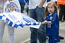© Licensed to London News Pictures. 07/05/2016. Leicester, UK. Leicester City fans celebrating outside the King Power stadium before their match with Everton before lifting the Premiership trophy. Pictured, a young fan waving the banner. Photo credit: Dave Warren/LNP