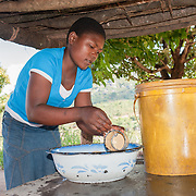 CAPTION: Erina washes dishes outside her home. More borehole pumps mean more people will have easier access to water for household use, as well as for agriculture. LOCATION: Nhamo Village, Bikita District, Masvingo Province, Zimbabwe. INDIVIDUAL(S) PHOTOGRAPHED: Erina Tapera.