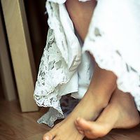 A photograph of a woman in a wedding dress with bare feet