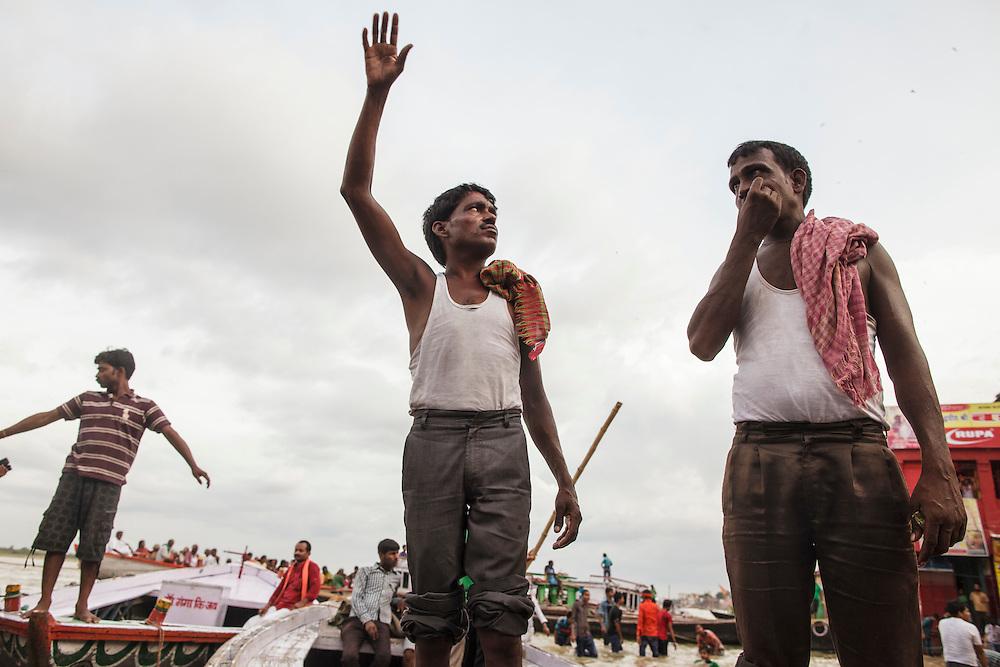Boatmen shouting for clients at Dashashwamedh Gath near Ganges River in Varanasi, India.