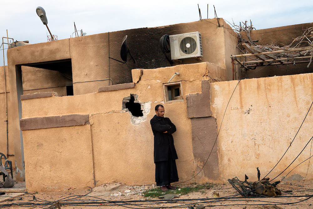 A man if front of an house because of the battle between rebels and pro Khaddafi forces.