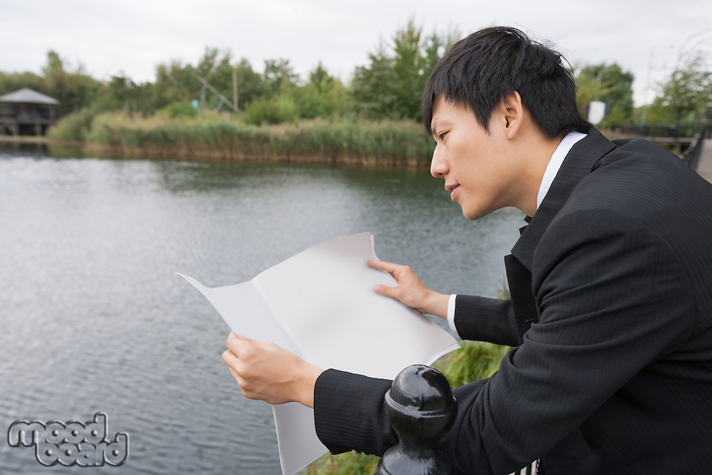 Side view of Asian businessman reading newspaper outside