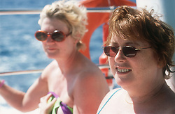Two women sunbathing on deck of boat during summer holiday,