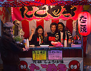 A young lady travelling in Japan posing at a street octopus-fritter stall.