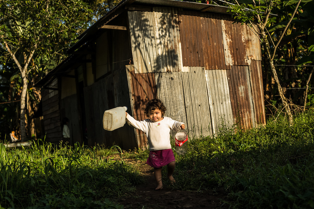 A girl runs out of her family's humble home to take empty jugs to a truck delivering clean water to residents of a small town where a nearby pineapple industrial farm operates.  Residents believe their water to be contaminated because of environmental failures at the pineapple plantation.
