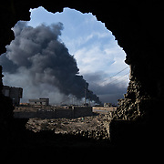 Seen from a building that has taken artillery fire, smoke billows from one of the remaining oil wells set ablaze by ISIL in their retreat from Qayyarah during the Mosul offensive in November, 2016.