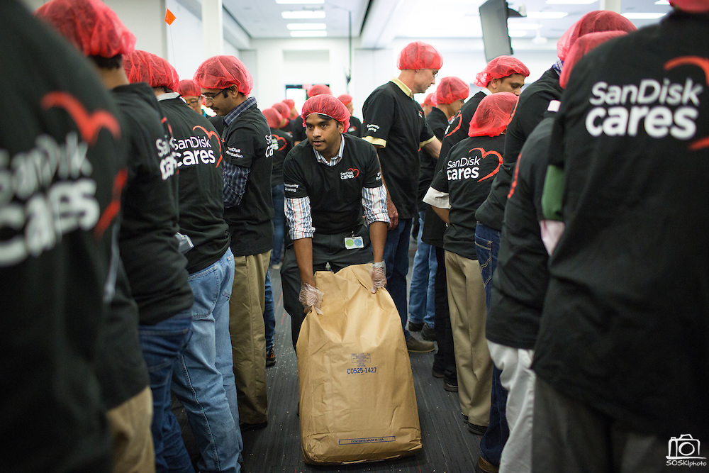 "A SanDisk employee drags a bag of soy in between volunteers during the Stop Hunger Now Foundation's ""Mayday, Mayday"" food-packing event at SanDisk Corporation in Milpitas, California, on May 13, 2014. (Stan Olszewski/SOSKIphoto)"