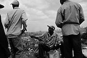 NAIROBI, KENYA - AUGUST 27, 2011: Pedestrians walk along the railroad tracks amid waste and pollution in Kibera slum.