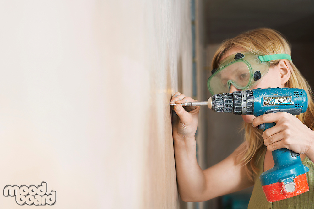 Woman wearing protective goggles drilling wall close-up