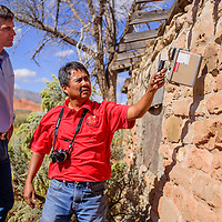 Melvin Yazzie shows Sen. Martin Heinrich how a Geiger counter spikes when held next to an abandoned dwelling  in Oak Springs Friday. Yazzie said the home had originally been constructed from stones removed from a uranium mine.