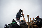 Migrants taking wood from a volunteers truck. Wood and gas are used to heat and to cook. Calais, France. FEDERICO SCOPPA/CAPTA
