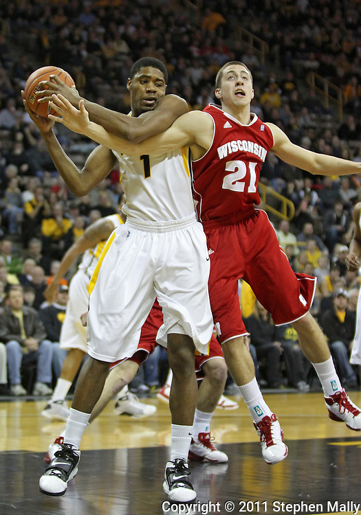 February 09 2011: Iowa Hawkeyes forward Melsahn Basabe (1) and Wisconsin Badgers guard Josh Gasser (21) battle for a rebound during the first half of an NCAA college basketball game at Carver-Hawkeye Arena in Iowa City, Iowa on February 9, 2011. Wisconsin defeated Iowa 62-59.