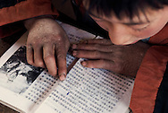 "A school kid during a reading lesson. The reading book is opened on Mao famous speech ""Serve the people"". The boy's hands show symptoms of malnutrition."