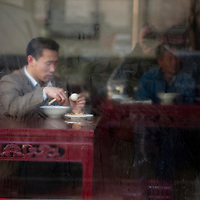 China, Beijing, View through steamy restaurant window of man cracking egg and eating from noodle bowl on cold spring morning