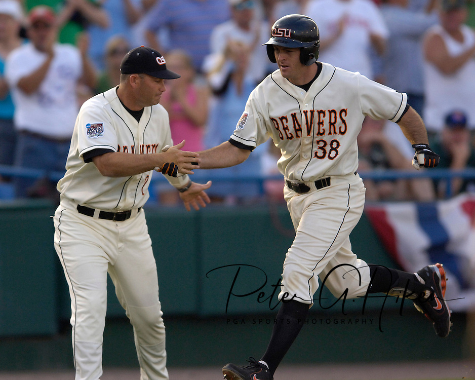 Oregon State's Bill Rowe (38) shakes third base coach Marty Lees as he rounds third base, after hitting a three-run homer in the fourth inning against  North Carolina.  Oregon State defeated North Carolina 11-7 in the second game of the Championship Series at the College World Series at Rosenblatt Stadium in Omaha, Nebraska, June 25, 2006.