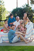 Multigenerational family with two girls and boy sitting on deck chair by swimming pool, portrait