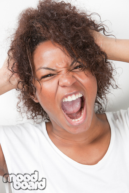 Portrait of frustrated young woman with hands in hair screaming against white background
