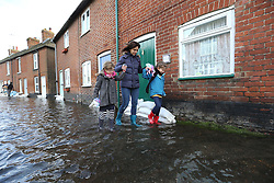 A young mother and her two daughters struggle through a flooded street in the village of Bridge, Kent , United Kingdom. Sunday, 9th February 2014. Picture by Stephen Lock / i-Images