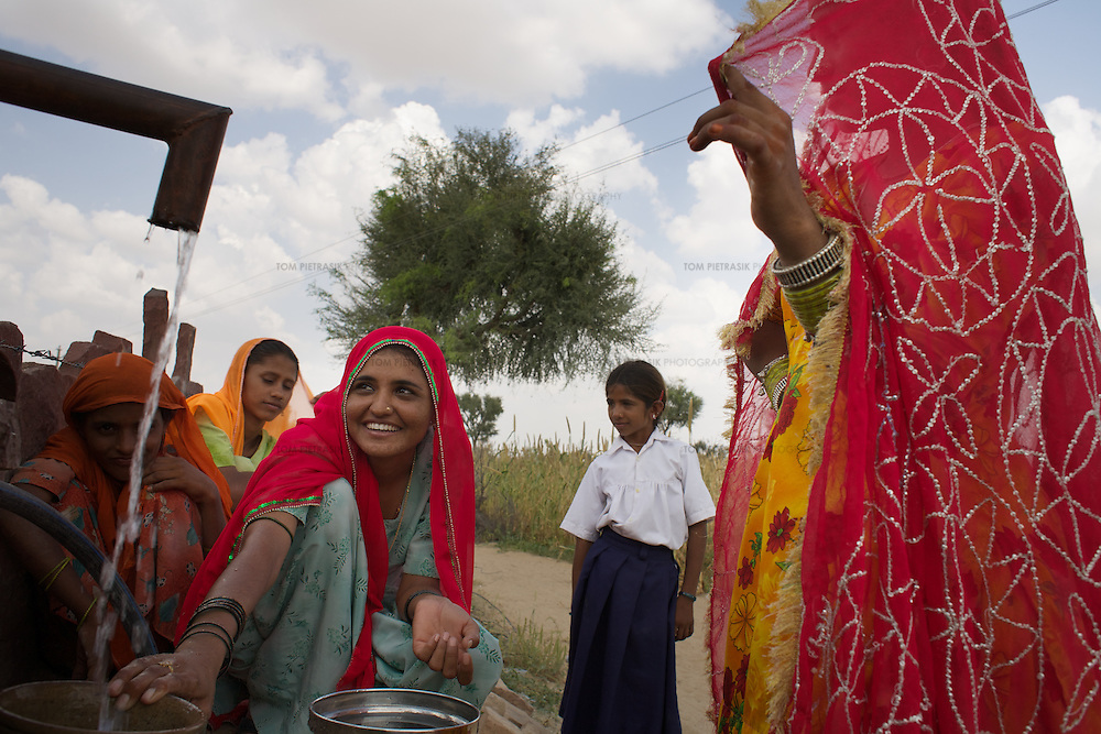 Dhouli Banoo, age 22 (in turquoise salwar with pink scarf), and other young women from Imam Nagar, collect water from their village tanka. This tanka (a covered tank surrounded by a catchment area of sloping gravel) was built by residents a year ago with the assistance of the Jal Bhagirathi Foundation (JBF), a non-governmental organization promoted by the United Nations Development Fund and the Italian Development Cooperation. Following the annual monsoon rains, the tanka will supply Imam Nagar's 60 resident's their drinking water needs for five months. When the tanka is exhausted, it becomes a storage facility for water delivered by truck. Women like Banoo used to walk 2-3km to collect water; the journey is now less than 100 meters. <br /> <br /> In five years since its inception the Jal Bhagirathi Foundation (JBF) has utilised traditional methods to revive more than 250 water harvesting structures in about 150 villages in Rajasthan's drought prone regions. JBF provides technical assistance and two-thirds the cost of a project, only after a village council has thoroughly discussed the issue and reached a unanimous decision. Villagers raise the initial funds by contributing according to their ability. The poor who cant spare any money offer free labour. By addressing the problem of water and uniting caste-ridden village communities, the water campaign has set in motion a silent revolution of far-reaching consequences. Infant mortality is going down. For women who have been liberated from the daily task of collecting water, literacy levels are on the rise. Stomach and skin ailments are showing signs of decrease. <br /> <br /> Photo: Tom Pietrasik<br /> Imam Nagar, Jodhpur District, Rajasthan. India<br /> September 17th 2007<br /> <br /> THIS PHOTOGRAPH IS THE COPYRIGHT OF TOM PIETRASIK. THE PHOTOGRAPH MAY NOT BE REPRODUCED IN ANY FORM OTHER THAN THAT FOR WHICH PERMISSION WAS GRANTED. THE PHOTOGRAPH MAY NOT BE MANIPULATED, STORED, OR DISTRIBUTED WITHOUT PRIOR PERMISSION FROM TOM PIETRASIK.<br /> <br /> Tom Pietrasik<br /> PHOTOGRAPH