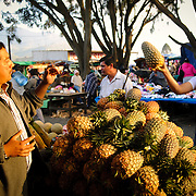 A customer buys a pineapple at the main market in Antigua, Guatemala.