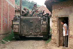 An ethnic Albanian watches American troops patrol through her village near Kololec where 2 Serbs were allegedly shot Monday, August 2, 1999 in Kosovo. (Photo by Ami Vitale)